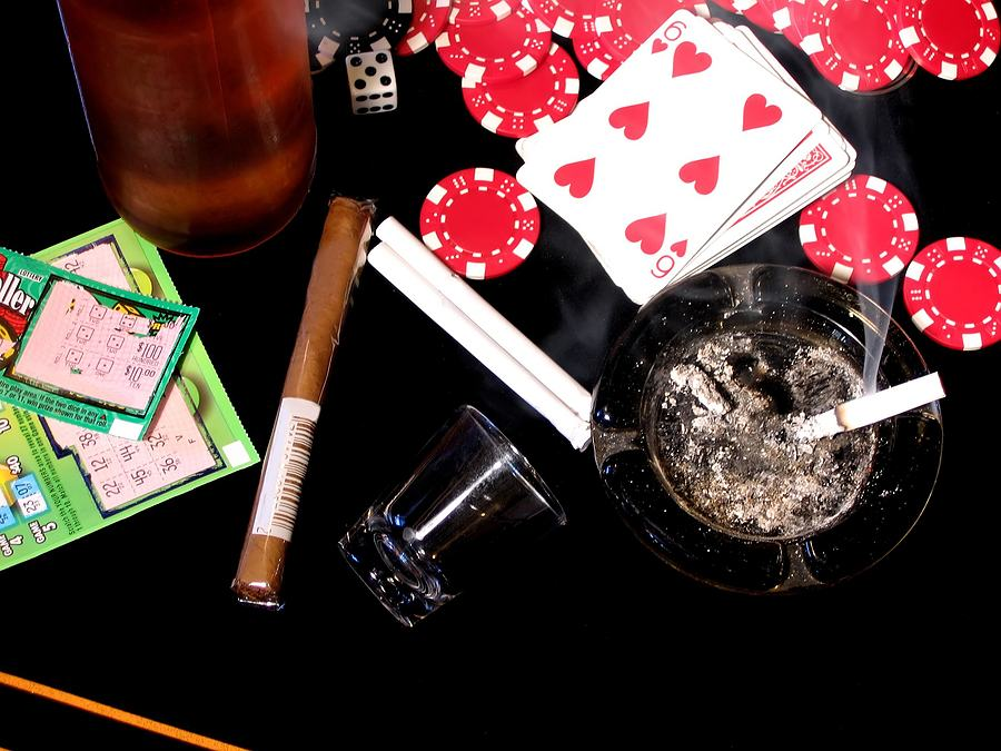 Various addictions laid out on poker table (numbers on tickets and UPC code have been altered or removed)